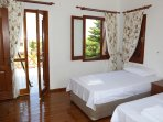 third bedroom with large twin beds, front balcony with sea views, rear window with mountain views