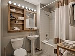 The updated bathroom offers a pedestal sink and a shower/tub combo.