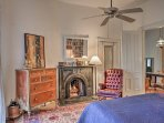 The first bedroom features a decorative fireplace, antique decor, and a large library of books.
