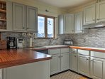 This fully equipped kitchen has modern appliances, ample counter space, and fashionable tile backsplash!