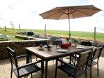 Terrasse privée côté champ avec barbecue Weber et parasol