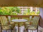 Surrounded by lush greenery the lanai is a relaxed space for morning coffee.