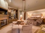 The cavernous Master Bedroom is complete with a king-size bed, a grand fireplace, and a flat screen TV.