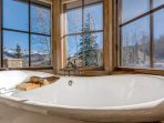 In the Master Bathroom, a traditional soaking tub sits below three panels of windows with gorgeous views.