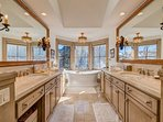 Separate vanities run the length of the Master Bathroom, lit by recessed lighting and ornate sconces.