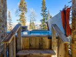 Relax in the hot tub amid the mountain trees.