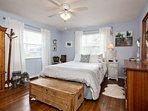 Bedroom features queen bed, long dresser, ceiling fan and alarm clock.