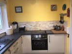 Modern fitted kitchen, with electric hob and cooker, microwave, slow cooker and washing machine.
