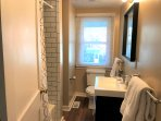 Updated second floor three piece bath with new tile, vanity, floors, and other upgrades!
