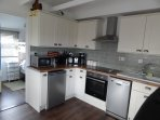 A modern , clean kitchen which is fully equipped - including a dishwasher.