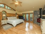 master bedroom with wood burning stove and flat screen tv