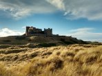 View of the imposing Bamburgh Castle from the footpath in the dunes