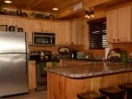 Well-equipped kitchen with seating for 4 at the kitchen counter.