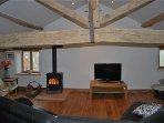 The large beamed lounge has plenty of comfortable seating, tv, DVDs, books, games and a log burner.