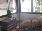 Back enclosed porch overlooks the park.  Serene and comfortable.  Relax here with a book and enjoy.