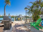 View of Waterway canal, Dock, colorful Adirondack Chairs & table and Weber Gas Grill