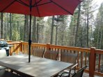 Private back deck with BBQ grill and beautiful forest scenery.