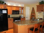 The kitchen is fully-equipped and features a granite-countertop.