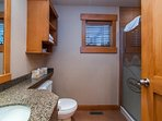 The full bathroom is spacious and features a lovely countertop and shower.