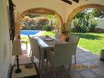 Vista del jardín y piscina desde el porche con comedor para 6 personas.