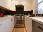 Sunny, modern, fully equipped kitchen also enjoys garden view.