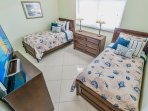 Guest bedroom with two twin beds and a big screen TV.
