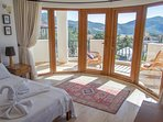 The first floor bedroom has a super king bed and large windows that lead onto the balcony