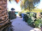 Side garden leading round to secluded pool and patio areas to the back of the bungalow