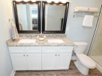 Granite counters and framed mirrors are present in each bathroom