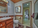 The second full bathroom has a shower/tub combo, single sink, and small vanity mirror.
