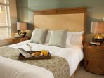 This bedroom is furnished with a plush, queen-sized bed