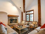 The living area is furnished with oversized plush sofas and gas fireplace.