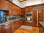 The fully equipped kitchen boasts a Wolf 5 burner gas stove and stainless double oven.