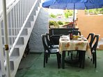 bbq, corner below apartment 12 stairs, table and six chairs