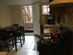 Kitchen open on to backyard with a privacy fence and includes a stove  microwave, and pots and pans.