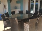 Outdoor terrace has a large 10 seater oval table.