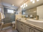Lower level renovated shared full bathroom with dual sinks and tile shower with rain shower head