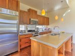 The kitchen houses stainless steel appliances and a custom-built center island.