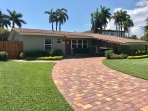 Paved horseshoe drive with covered carport. Palm tree lines street. Quiet neighborhood
