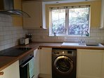Kitchen with washing machine, dish washer and modern hob and oven.