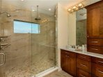 King Master Bath with two shower heads and view of the bay, dual sinks, and private toilet room.
