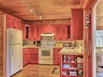 The fully equipped kitchen is finished in a welcoming pop of color!