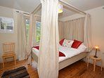 Four-poster bed with views out of the window across the countryside