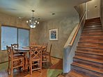 The dining room is located next to the staircase that leads upstairs.