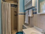The en-suite bathroom has a stand-up shower, porcelain sink, and a single vanity mirror.