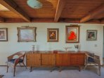 Original artwork and mid-century modern credenzas in dining area.