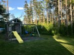 Large play structure with playhouse, slide, sandbox, baby swing, 2 children's swings and glider.