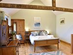 Master bedroom with vaulted ceiling and original beams.