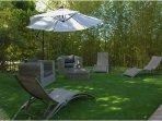 De nombreux transats et fauteuils pour profiter du jardin soleil ou ombre