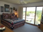 Queen size bed and full wall or windows in the master bedroom.